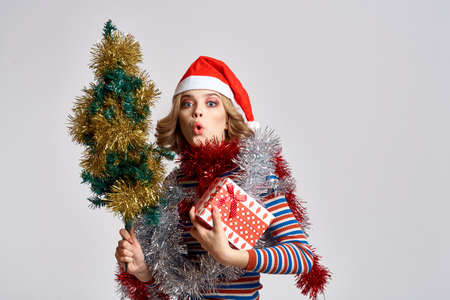 woman with a Christmas tree and gifts cap light background model New Year Stockfoto