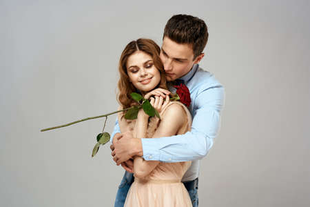 Cheerful young couple romance embrace relationship red rose lifestyle light background