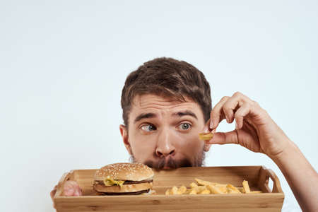 man with wooden tray fries and hamburger fast food calories model white t-shirt Stockfoto