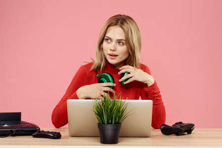 woman in headphones with gamepad in front of laptop sit at table entertainment lifestyle pink background