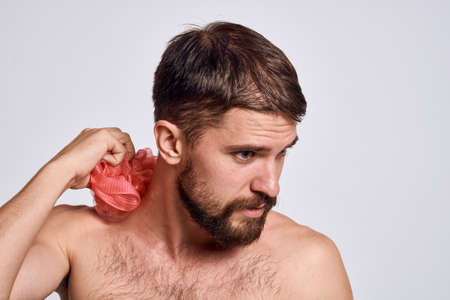 A man with bare shoulders a washcloth in his hands clean skin taking a shower light background