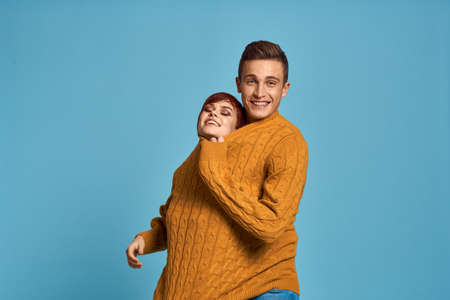 couple in yellow sweater posing against blue background cropped view