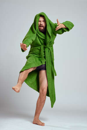emotional man in a green robe on a light background in full growth fun emotions model