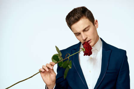 A man in a suit with a rose in his hands a gift date light background