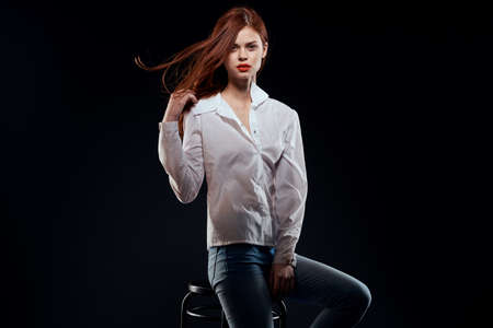 pretty woman sitting on a chair posing white shirt jeans long hair red lips dark background Archivio Fotografico