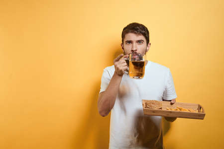 Bearded man with mug of beer fast food diet food fun alcohol lifestyle yellow background