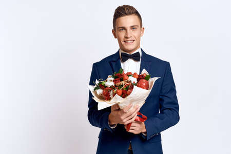 An elegant man in a classic suit with a bow tie holds a bouquet of flowers in his hand Stockfoto