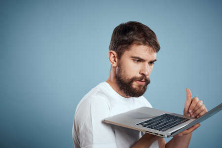 Emotional man with laptop in hands on blue background monitor keyboard internet model cropped view