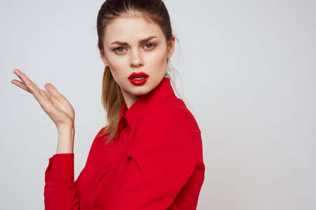 portrait of a woman with red lips in a shirt on a light background cropped view model makeup hairstyle