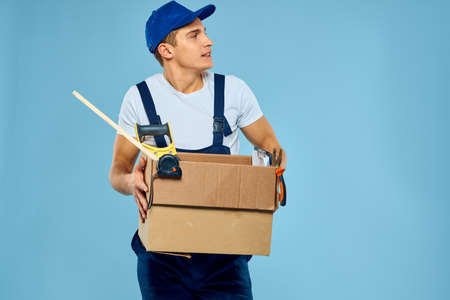 working man in uniform box with tools loader delivery blue background