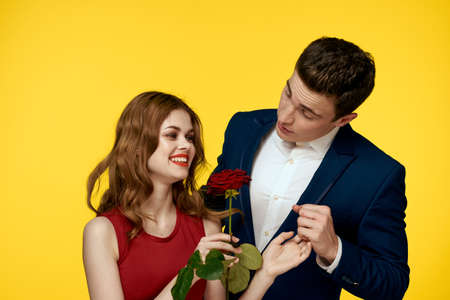 lovers man and woman with a red rose in their hands hugging on a yellow background romance relationship love family