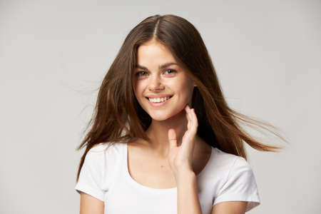 Happy brunette smiling and touching her face with hand front view