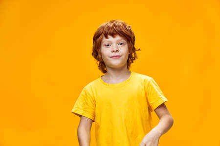 Boy red hair yellow t-shirt isolated background cropped view Stockfoto