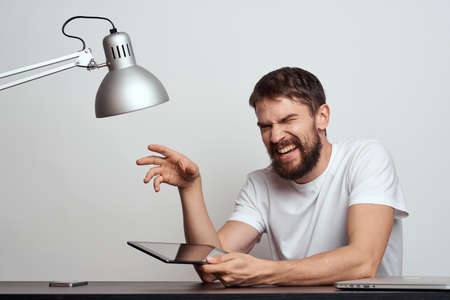 A man with a tablet at the table gestures with his hands on a light background and an iron lamp