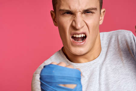 Sporty man in blue boxing gloves and a T-shirt on a pink background practicing punches cropped view Stockfoto