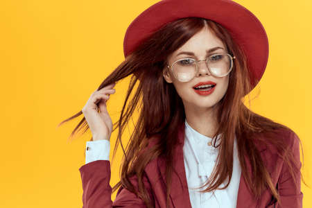 woman in red hat jacket glasses yellow background cosmetics