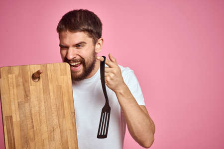 guy holding kitchen board and spatula in hand on pink background cropped view Stockfoto