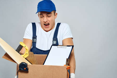 man in working uniform with a box in his hands tools loader delivery light background