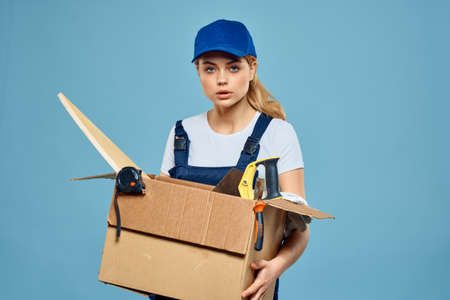 Working woman in uniform with box in hands tools loading delivery service blue background