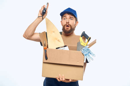 Worker man in uniform with a box in his hands tools delivery service light background