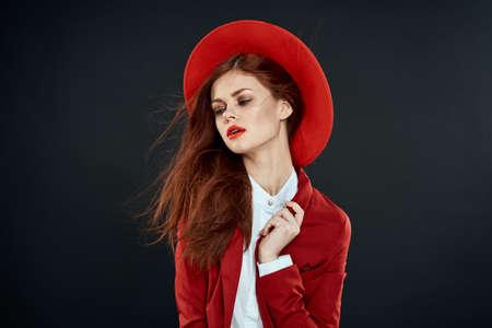 Elegant woman in red hat blazer glamor lifestyle cropped view dark background Stockfoto