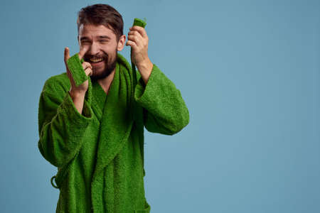 Bearded man in green robe with belt on blue background cropped view of emotion