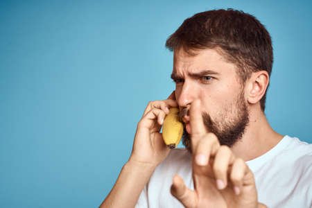 a man with a banana is caught in a white t-shirt on a blue background concept of communication by phone Reklamní fotografie