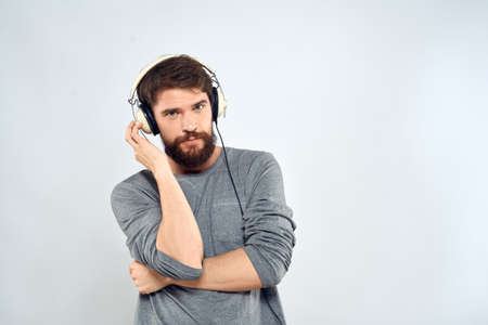 Man in headphones listens to music lifestyle leisure light background