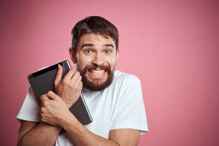 Man advertises a tablet on a pink background codes Space cropped view of emotions white t-shirt model new technologies
