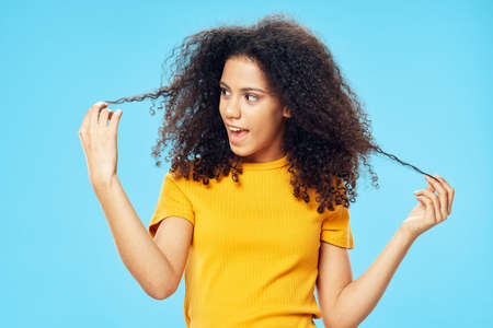 Woman holding curly black hair in her hands yellow t-shirt smile emotions close-up