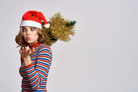 woman with a Christmas tree in her hand yellow tinsel holidays cap gifts New year light background cropped view