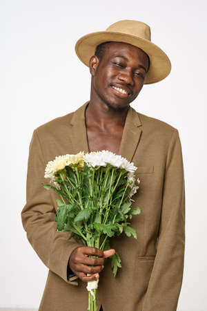 Man with a bouquet of flowers in a hat smile African appearance 版權商用圖片