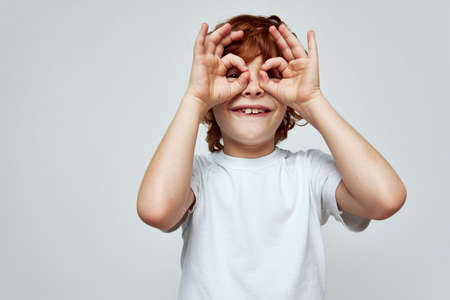 Grimacing boy holds his hands near his face and in the form of a mask smile childhood