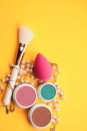 Eyeshadows and makeup brushes on a yellow background top view professional cosmetics