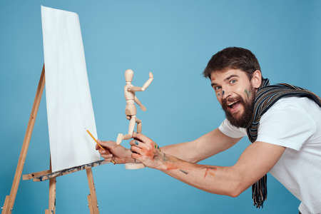 Male artist with a wooden dummy in hands drawing Creative hobby blue background