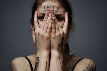 woman with offensive inscriptions on her body touching herself with hands stress frustration hate