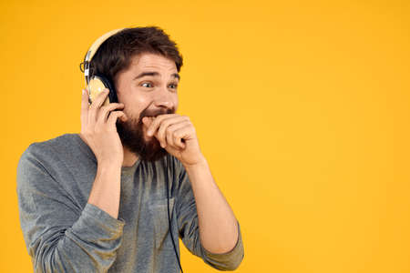 Man in headphones listens to music technology lifestyle fun people yellow background