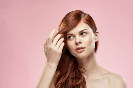 woman holding hair with hand problems hairstyle care emotions shoulders pink background