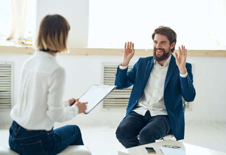 a man explains something to a woman to a psychologist indoors near a window