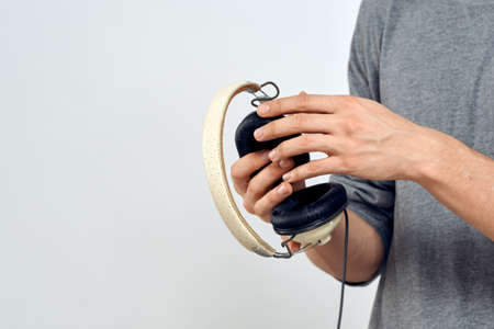 Man holding headphones in the hands of a man lifestyle modern style technology cropped view 版權商用圖片