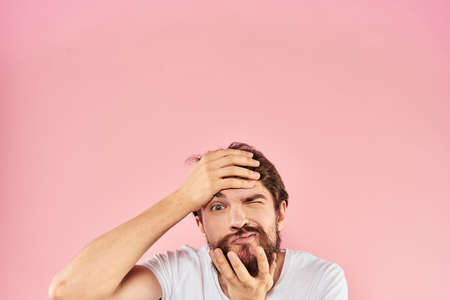 Bearded man in white t-shirt gesturing with hands facial expression close up pink background
