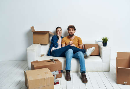 Young married couple in a new apartment on a white couch boxes with things moving