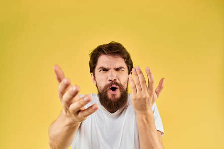 A man in a white t-shirt gestures with his hands lifestyle cropped view yellow background more fun