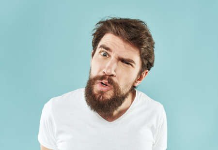 Aggressive man with a beard on a blue background cropped view Archivio Fotografico