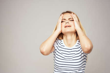 A woman in a striped T-shirt holds her hands in front of her emotions displeasure light background