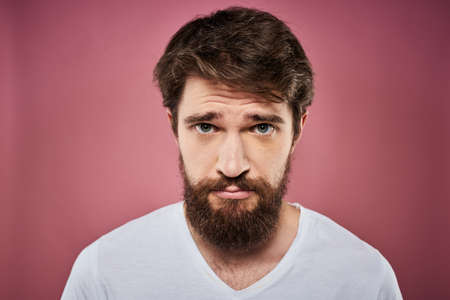Emotional bearded man in white T-shirt discontent pink background Archivio Fotografico