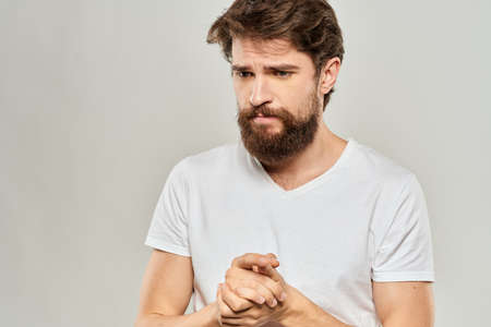 bearded man gesturing with his hands in a white t-shirt aggression light background
