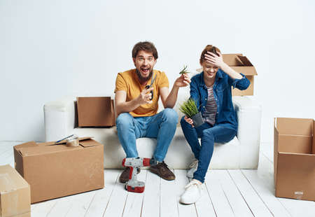 Man and woman sit on white couch boxes with moving lifestyle things