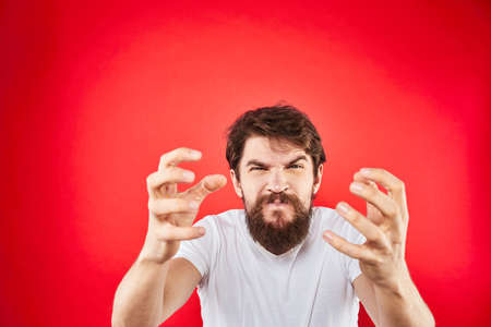Emotional bearded man gestures with his hands in a white T-shirt aggression discontent red background Archivio Fotografico