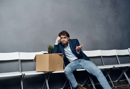 Man sits on a chair box with things dismissing discontent depression
